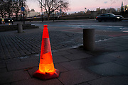 Red traffic cone placed onto a floor light and glowing on the street in London, United Kingdom.