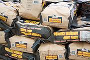 Piled bags of mesquite lump charcoal, UK