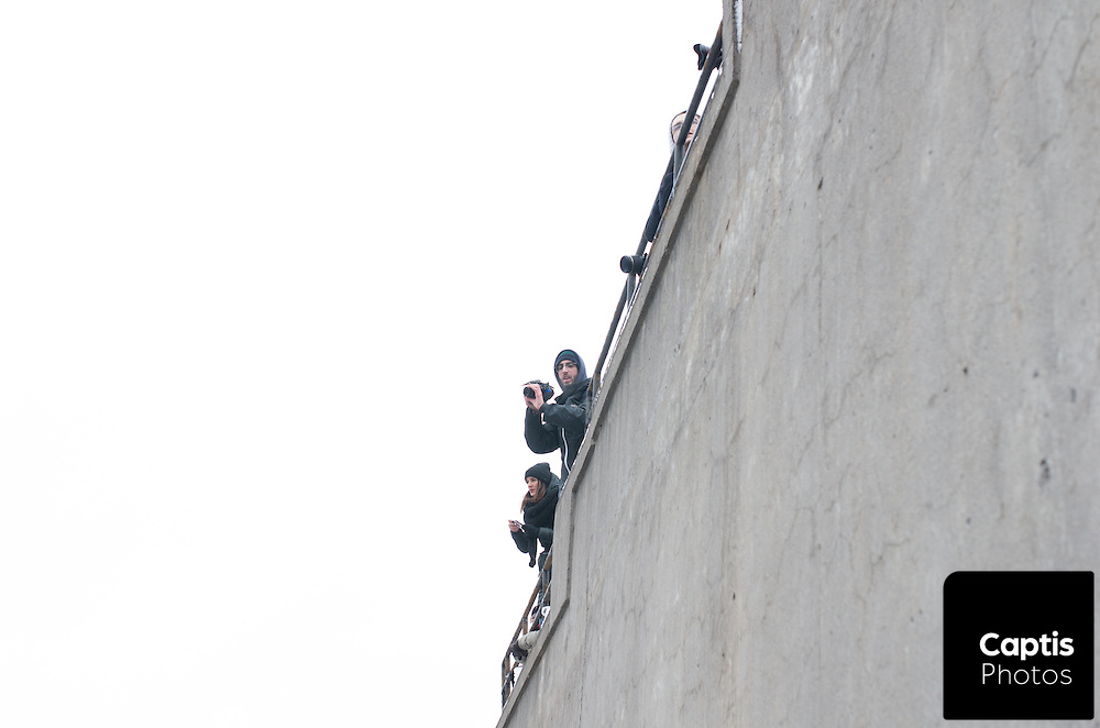 A man film a group of encircled protesters from above. March 15, 2015.