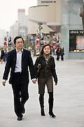 Couple walking on Nanjing Road, central Shanghai, China