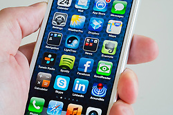 Close-up detail of man holding new iPhone 5 smart phone showing screen with many apps