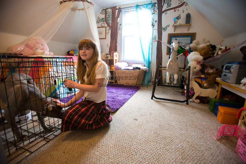 Rya Hickey, daughter of Margaret B. Jones in her bedroom with her pet pit bull, Flue.  Margaret painted the trees on the wall in the room.