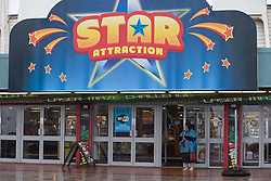 """© Licensed to London News Pictures . 17/06/2015. Blackpool  , UK . A woman in a plastic poncho takes in the doorway of """" Star Attraction """" on Blackpool Promenade . Rain and fog over Blackpool today ( Wednesday 17th June 2015 ) . Photo credit : Joel Goodman/LNP"""