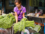 22 MARCH 2016 - BANGKOK, THAILAND:  A woman sells long beans in the flower market. Many of the sidewalk vendors around Pak Khlong Talat, the Bangkok flower market, closed their stalls Monday. As a part of the military government sponsored initiative to clean up Bangkok, city officials announced new rules for the sidewalk vendors that shortened their hours and changed the regulations they worked under. Some vendors said the new rules were confusing and too limiting and most vendors chose to close Monday rather than risk fines and penalties. Many hope to reopen when the situation is clarified.        PHOTO BY JACK KURTZ