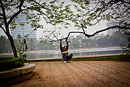An old man exercises with the help of a tree by the lake in Lenin Park, Hanoi, Vietnam