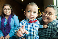 Zoilo Chacon-Maldonado, 17-months-old, hangs out with his newly adoptive parents Jessica Chacon, left, and Liza Maldonado on Monday during a local adoption event in celebration of November being National Adoption Month. The event is organized by the CYFD Foster Care/Adoptions Licensing Unit and 3rd Judicial District Court Chief Judge Fernando Macias.