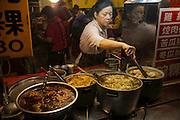 Vendors prepare food for sale at the LongShan night market in Teipei, Taiwan.