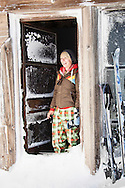 A smiling woman stands in the frosty door frame of the Silcox Hut on Mt. Hood, Oregon.