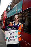 Hackney London February 10th 2016. Second one day strike by junior doctors  protesting against proposed changes to their contract including payment for working on Saturdays. Picket at Hackney Town Hall . A member of Unison holds a placard encouraging drivers to toot their support.