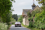 Motorist driving 1961 British made Alvis TD21 DHC Series 1 drophead ooupe classic car in Swinbrook village, The Cotswolds, England