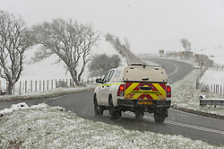© Licensed to London News Pictures. 12/04/2021. Llanfihangel Nant Melan, Powys, Wales, UK. A motorist drives through an unseasonal wintry landscape on the A44 road near Llanfihangel nant Melan in Powys, Wales, UK. Photo credit: Graham M. Lawrence/LNP