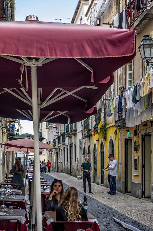 View down a narrow street typical of Lisbon, with restaurants, laundry hanging out to dry, and cobblestones.