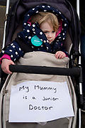 Homerton hospital, Hackney, London. February 10th 2016. Second one day strike by junior doctors  protesting against proposed changes to their contract including payment for working on Saturdays. A baby girl in her pram with a sign saying 'My mummy is a junior doctor'.
