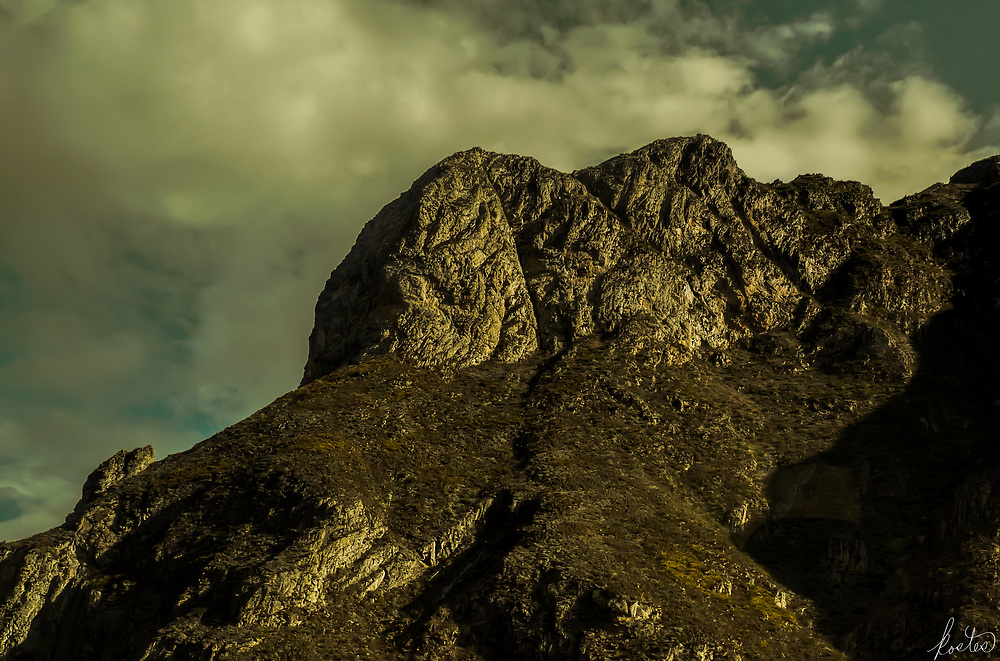 A outcrop of rock, in the golden hour in the Andes with dramatic clouds.