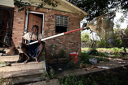 29 August 2006. New Orleans, Louisiana. Lower 9th ward. <br /> On the one year anniversary of hurricane Katrina, and most of the area remains derelict and abandoned. Resident Terry Charles moved back into his flood ravaged home months ago and lives in his mould filled home from which he was lucky to escape when the hurricane hit. Terry suffers from severe mental problems, yet somehow manages to live alone with no neighbours or community. He has not eaten for days. He holds a net he made, in which he 'catches things.' The net contained a flood damaged rusty cigarette lighter and various bits of junk. There are no social services to help Terry. He can quote passages from the bible and scratches bizarre drawings on bits of paper he finds. Terry needs help desperately, but none is available to him. He does not know it is the one year anniversary today.<br /> Photo Credit©; Charlie Varley/varleypix.com