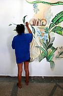 Woman painting a mural in Gibara, Holguin Province, Cuba.