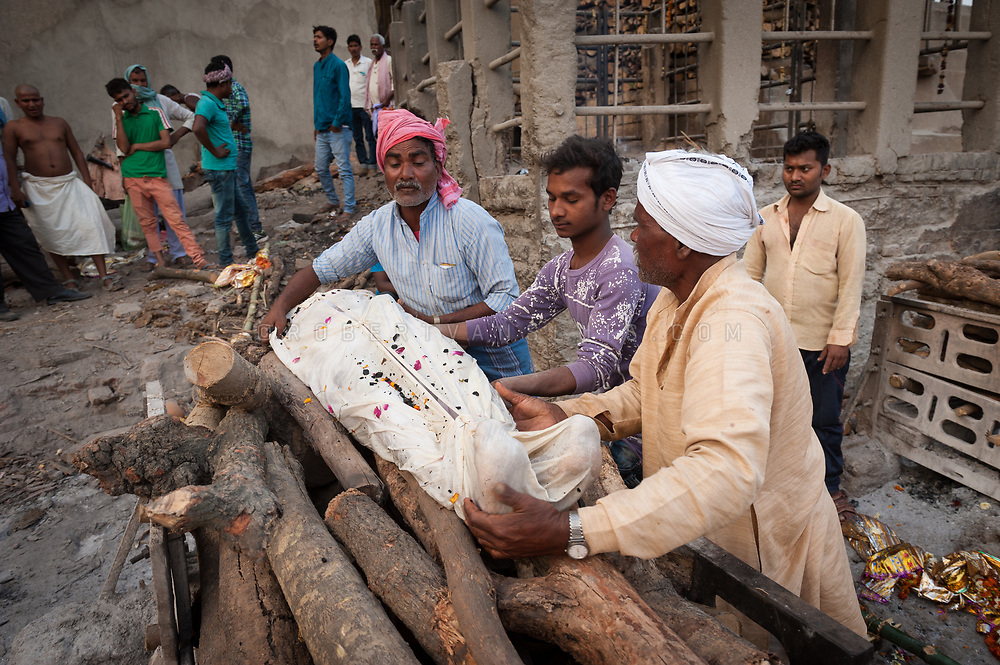 Family members put a body on a funeral pyre at Manikarnika cremation ground, Varanasi, India. Photo © robertvansluis.com