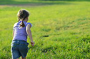 Girl of six runs away from camera in a green field