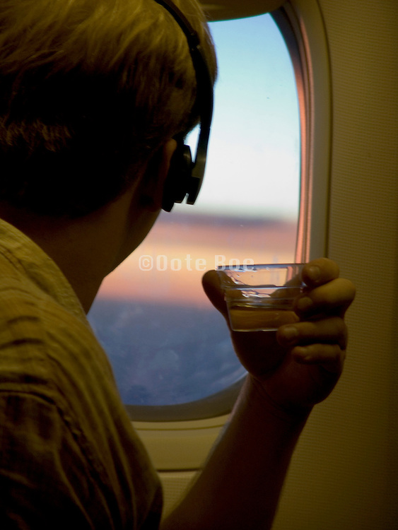 passenger with headphones on and cup in hand watching the sun from within a airplane