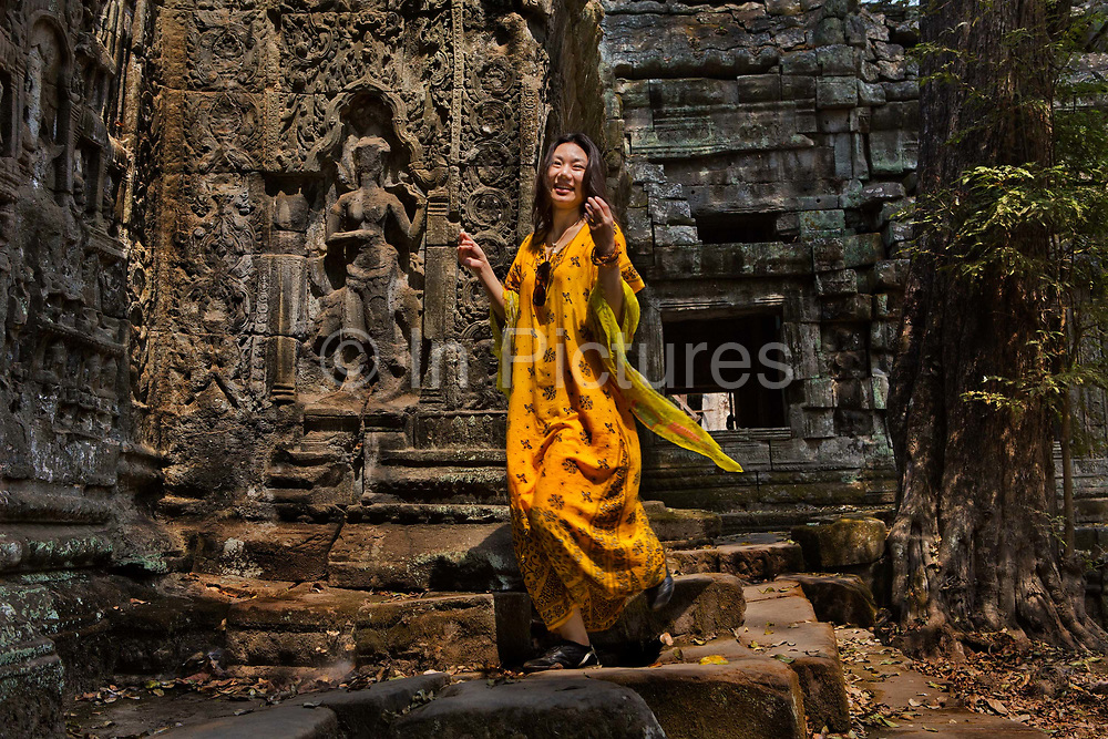 Chinese woman modelling clothes in temple ruins, Ta Prohm, Angkor temple complex. <br /> Unlike most of the temples of Angkor, Ta Prohm has been largely left to the clutches of the living jungle. With its dynamic interaction between nature and man-made art, this atmospheric temple is a favorite for many - who can't help but feel a little like Indiana Jones or Lara Croft (which was filmed here) as they pick through the rubble.<br /> Construction on Ta Prohm began in 1186 AD. Originally known as Rajavihara (Monastery of the King), Ta Prohm was a Buddhist temple dedicated to the mother of King Jayavarman VII.