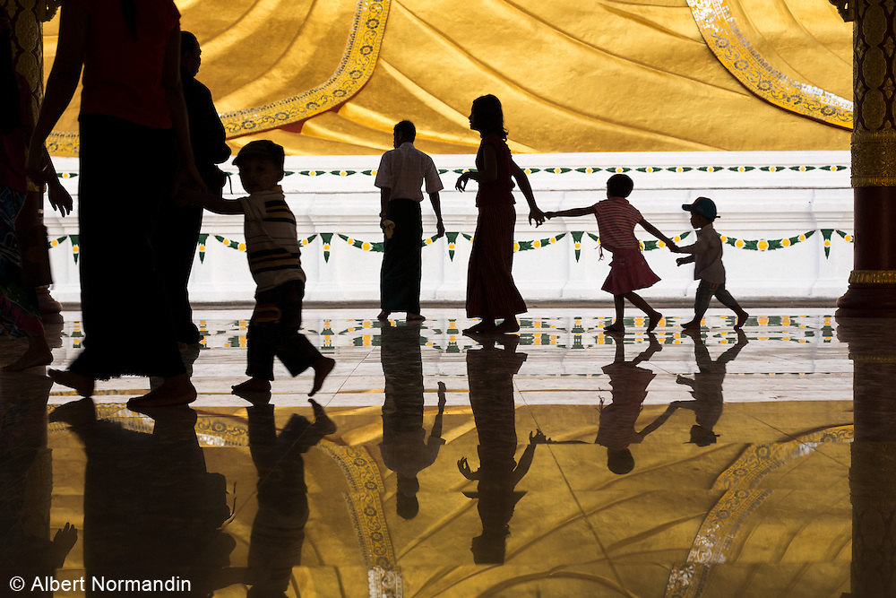 People in silhouette walking and holding hands in reflection of Reclining Buddha, Dawei