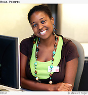 Environmental portrait of an African American woman at her work desk.