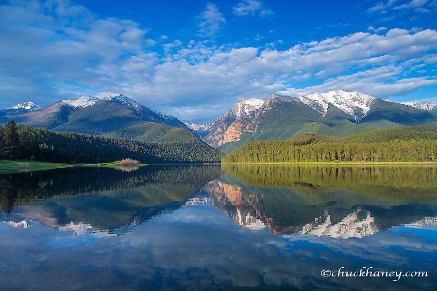 Mission Reservoir reflecting peaks of the Mission Mountains near St Ignatius, Montana, USA