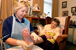 Home help worker visiting an elderly woman to change the dressings on her feet UK