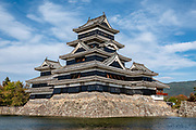 "Matsumoto Castle, built 1592-1614 in Nagano Prefecture, Japan. The castle was built from 1592-1614 in Matsumoto, Nagano Prefecture, Japan. Matsumoto Castle is a ""hirajiro"" - a castle built on plains rather than on a hill or mountain, in Matsumoto. Matsumotojo's main castle keep and its smaller, second donjon were built from 1592 to 1614, well-fortified as peace was not yet fully achieved at the time. In 1635, when military threats had ceased, a third, barely defended turret and another for moon viewing were added to the castle. Interesting features of the castle include steep wooden stairs, openings to drop stones onto invaders, openings for archers, as well as an observation deck at the top, sixth floor of the main keep with views over the Matsumoto city."
