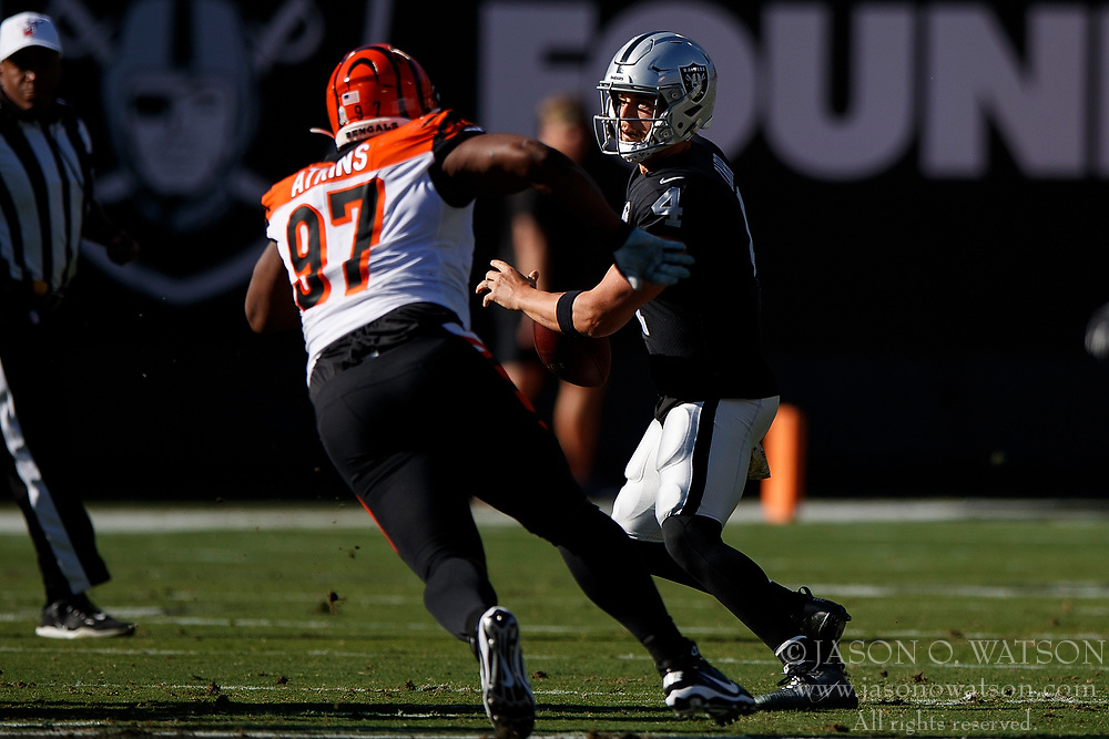 OAKLAND, CA - NOVEMBER 17: Quarterback Derek Carr #4 of the Oakland Raiders is sacked by defensive tackle Geno Atkins #97 of the Cincinnati Bengals during the first quarter at RingCentral Coliseum on November 17, 2019 in Oakland, California. (Photo by Jason O. Watson/Getty Images) *** Local Caption *** Derek Carr; Geno Atkins