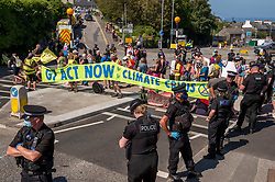 """© Licensed to London News Pictures; 13/06/2021; St Ives, Cornwall UK. G7 summit in Cornwall. Police hold their lines as protesters hold a long banner saying G7 Act Now Climate Crisis"""" as Extinction Rebellion block the main road out of St Ives on the last day of the summit, protesting against climate change and what they say is not enough action by world leaders including those attending the G7.. Photo credit: Simon Chapman/LNP."""