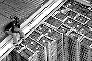 Man sitting by stacks of pineapples crates on the lower deck of a cargo boat.