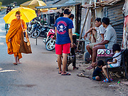 "15 FEBRUARY 2019 - SIHANOUKVILLE, CAMBODIA: A Buddhist monk walks through a migrant camp in Sihanoukville during his morning alms rounds. Families who live in the shanty town came to Sihanoukville from other Cambodian provinces because of the town's booming economy and construction industry building Chinese resorts and casinos. There are about 80 Chinese casinos and resort hotels open in Sihanoukville and dozens more under construction. The casinos are changing the city, once a sleepy port on Southeast Asia's ""backpacker trail"" into a booming city. The change is coming with a cost though. Many Cambodian residents of Sihanoukville  have lost their homes to make way for the casinos and the jobs are going to Chinese workers, brought in to build casinos and work in the casinos.      PHOTO BY JACK KURTZ"