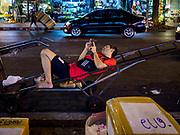 27 FEBRUARY 2019 - BANGKOK, THAILAND: A porter in the Bangkok flower market, lays on his handtruck while he checks his smart phone while he waits for customers. Bangkok, a city of about 14 million, is famous for its raucous nightlife. But Bangkok's real nightlife is seen in its markets and street stalls, many of which are open through the night.        PHOTO BY JACK KURTZ