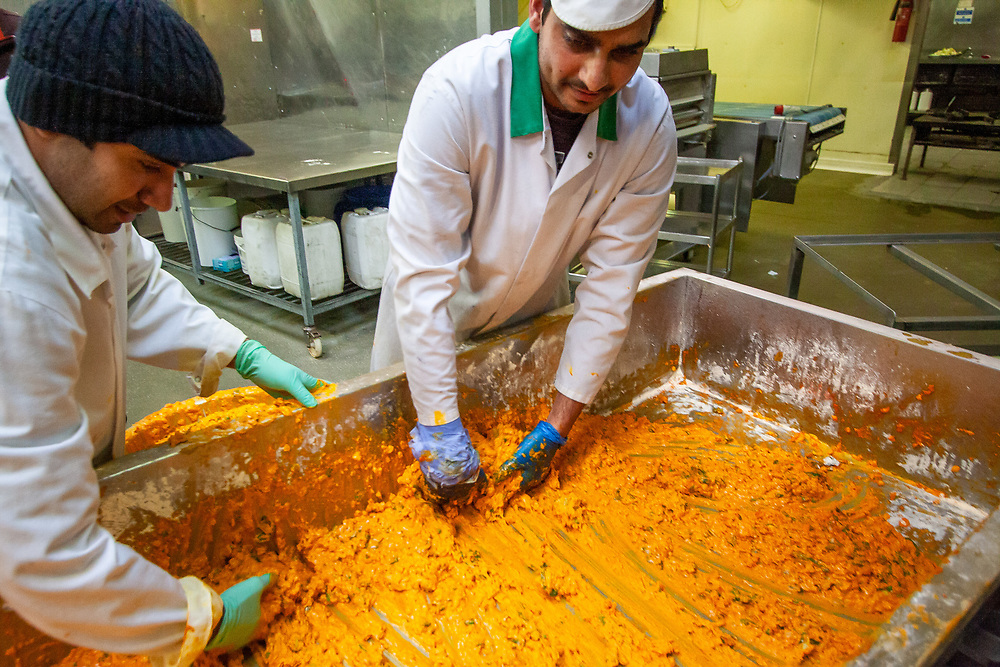 Southall, United Kingdom   2010<br /> Workers scrape turmeric- and spice-infused batter into a tub before it is deep fried and turned into pakoras, the spicy snack, and distributed for sale throughout the UK.
