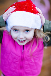 Close up of a girl wearing a red and white Chistmas hat with her hands on her head