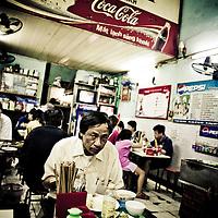 Man eating Pho in noodle shop, French Quarter, Hanoi, Vietnam