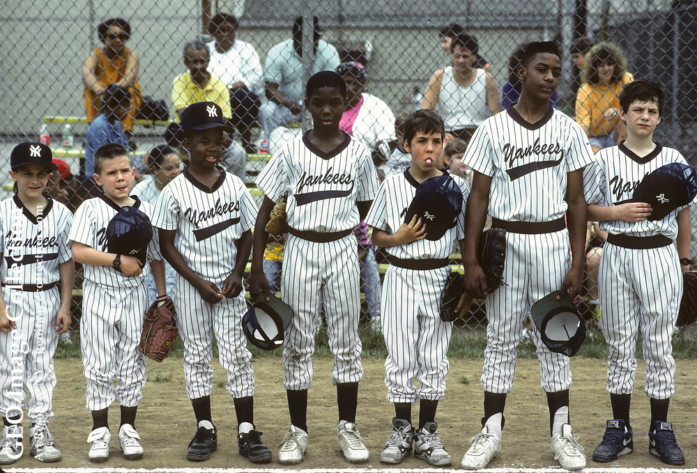 Opening day of Little League baseball season in Hazelwood, a neighborhood of Pittsburgh. The Sunday afternoon event is an annual rite of spring in this working class town. Boys in stripped baseball uniforms stand and fidget as the National Anthem is played at the opening ceremony.