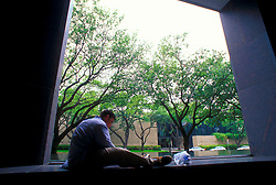 Stock photo of a student reading on campus