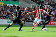 Stoke city's Charlie Adam © looks to go past Mile Jedinak (15) and Jose Campana ® of Palace. Barclays Premier league match, Stoke city v Crystal Palace at the Britannia Stadium in Stoke on Trent on Saturday 24th August 2013. pic by Andrew Orchard , Andrew Orchard sports photography,