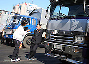 A North Korean truck driver talks with a Chinese business woman at the customs station in Dandong China, on the Sino-DPRK border October 11, 2006.  DPRK, north korea, china, dandong, border, liaoning, democratic, people's, rebiblic, of, korea, nuclear, test, rice, japan, arms, race, weapons, stalinist, communist, kin jong il