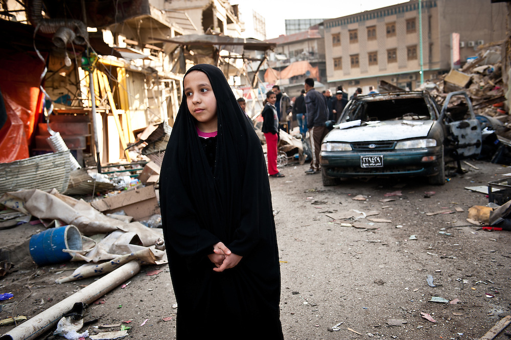 A young girl stands in a street in the Kadhimiya neighborhood of Baghdad where an car bomb the previous day killed fifteen civilians.