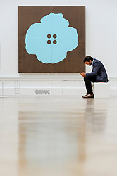 """© Licensed to London News Pictures. 08/06/2017. London, UK. A visitor sits in front of """"Aqua Button Flower June 30 2015"""" by Donald Sultan.  Preview of the Summer Exhibition 2017 at the Royal Academy of Arts in Piccadilly.  Co-ordinated by Royal Academician Eileen Cooper, the 249th Summer Exhibition is the world's largest open submission exhibition with around 1,100 works on display by high profile and up and coming artists.<br />  Photo credit : Stephen Chung/LNP"""