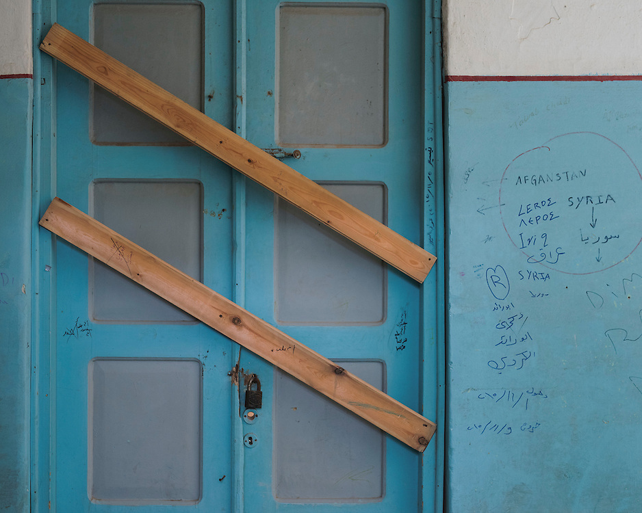 A boarded up door and graffiti at the closed down refugee camp at the Port of Lakki. <br /> <br /> The camp was opened by volunteers in the summer of 2015 and later that year UNHCR and MSF expanded it and provided additional tents, toilets and other facilities. The camp was closed soon after the opening of a 'Hotspot' (EU-run migrant's reception centres) camp in Lepida in February 2016.