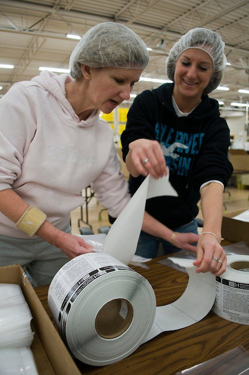 Mary Quentin (left) and Coleen Krechel place labels on the meal bags.