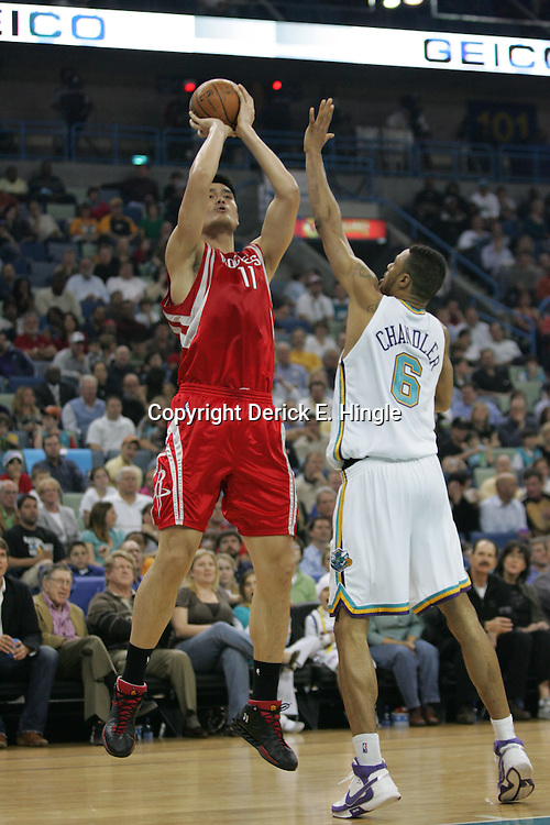 Yao Ming#11  of the Houston Rockets gets off a shot as Tyson Chandler #6 for the New Orleans Hornets defends on February 22, 2008 in a game against the Houston Rockets at the New Orleans Arena in New Orleans, Louisiana. .