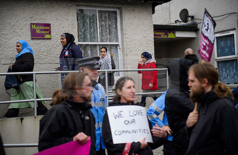 **NOTE TO EDITORS: An young people are pictured in the image** © Licensed to London News Pictures. 07/01/2017. London, UK. A group of young people leave Mote Road Islamic centre mosque in Maidstone, Kent (rear) as members of Kent Anti-Racism Network counter protest against far-right group The South East Alliance protesting against the expansion of the mosque . Plans to redevelop Maidstone Mosque into a purpose-built centre with three shops have been approved by  Maidstone Borough Council. A counter demonstration is Organised by The Kent Anti-Racism Network. . Photo credit: Ben Cawthra/LNP