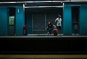 Travellers waiting for a train to Placa Catalunya, at Gracia Metro Station, Barcelona.