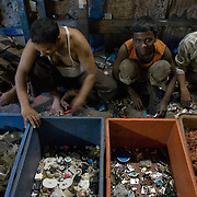 workers sift through piles of plastic waste at a typical recycling enterprize in Dharavi.