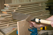 Female carpenter uses a Dozuki Japanese saw the double blade Ryoba to create a finger joint